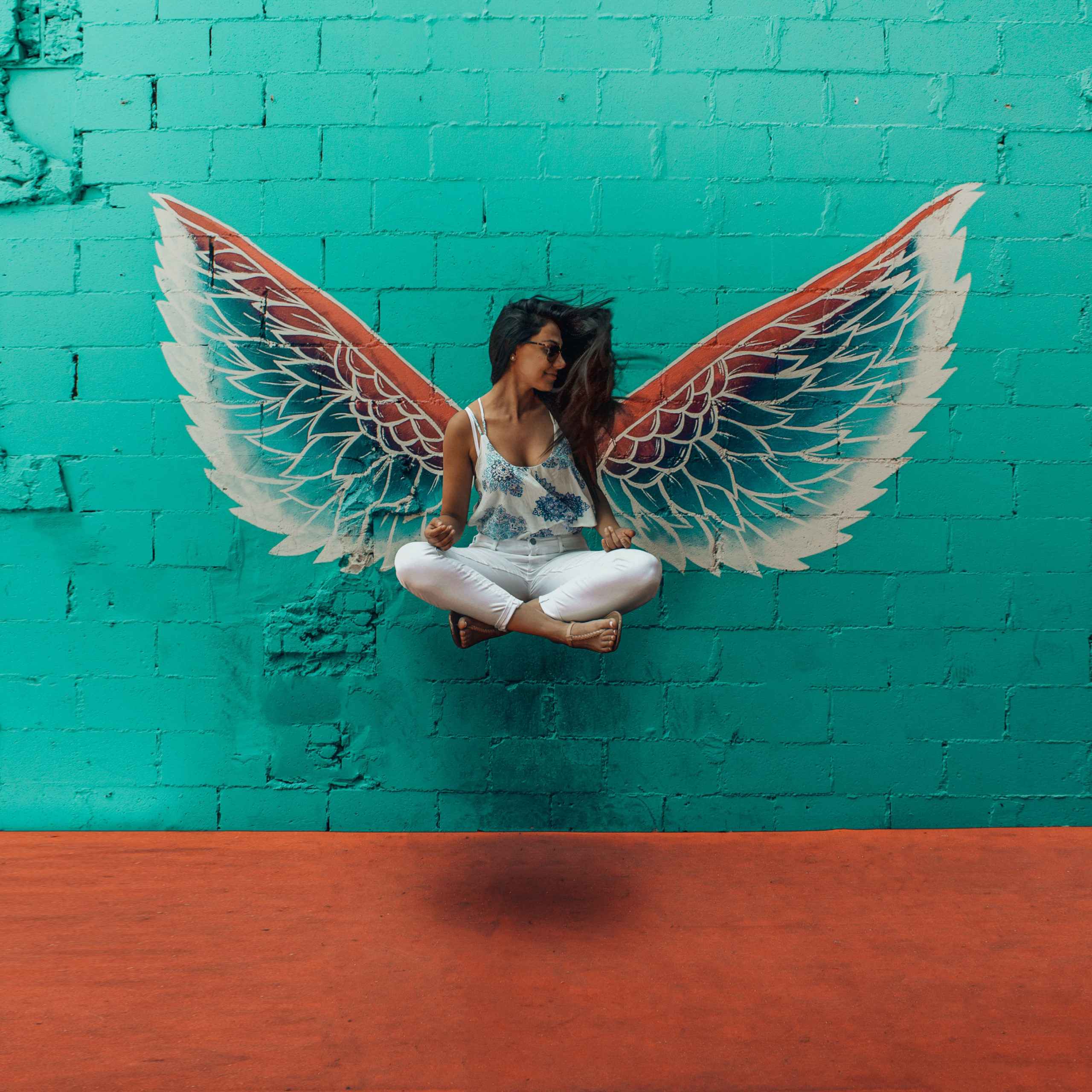 Woman in seated position floats in front of graffiti angel wings