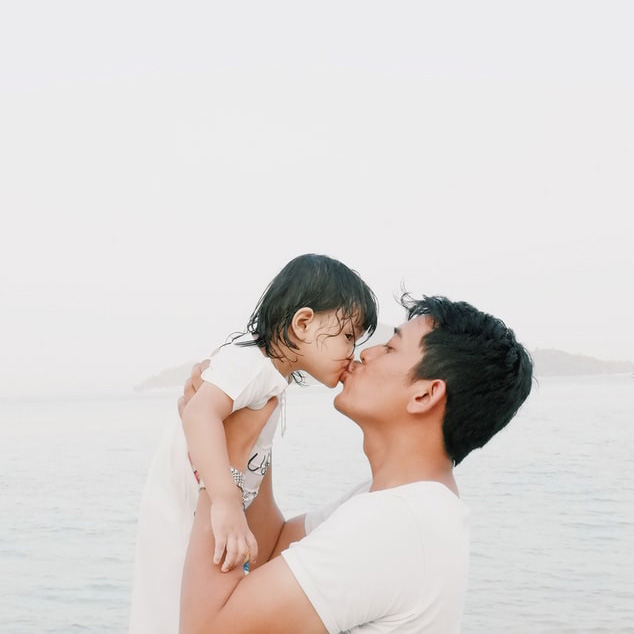 Dad kissing child by Devi Yahya via Unsplash