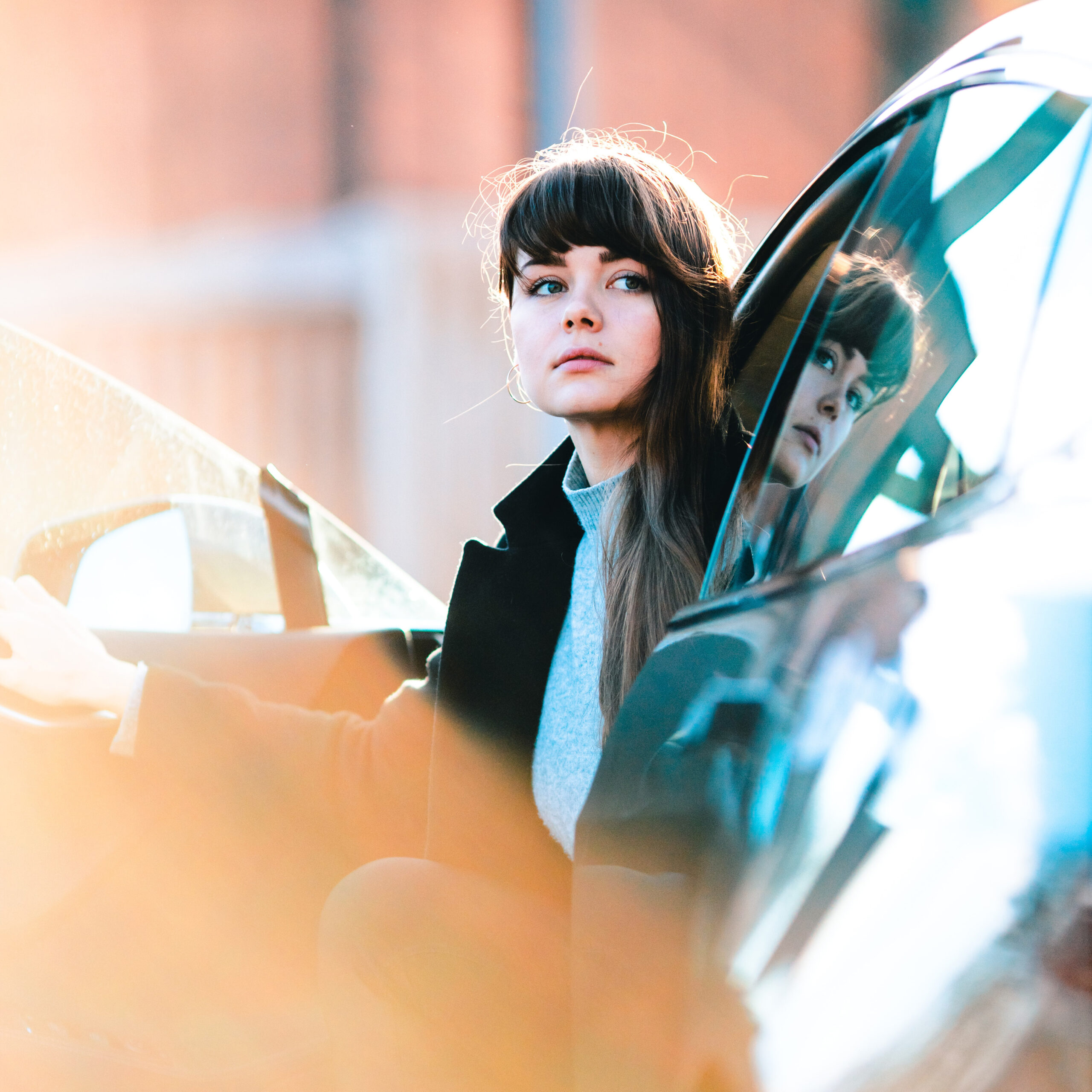 Woman sitting in the open driver side door of a car by Taneli Lahtinen via Unsplash