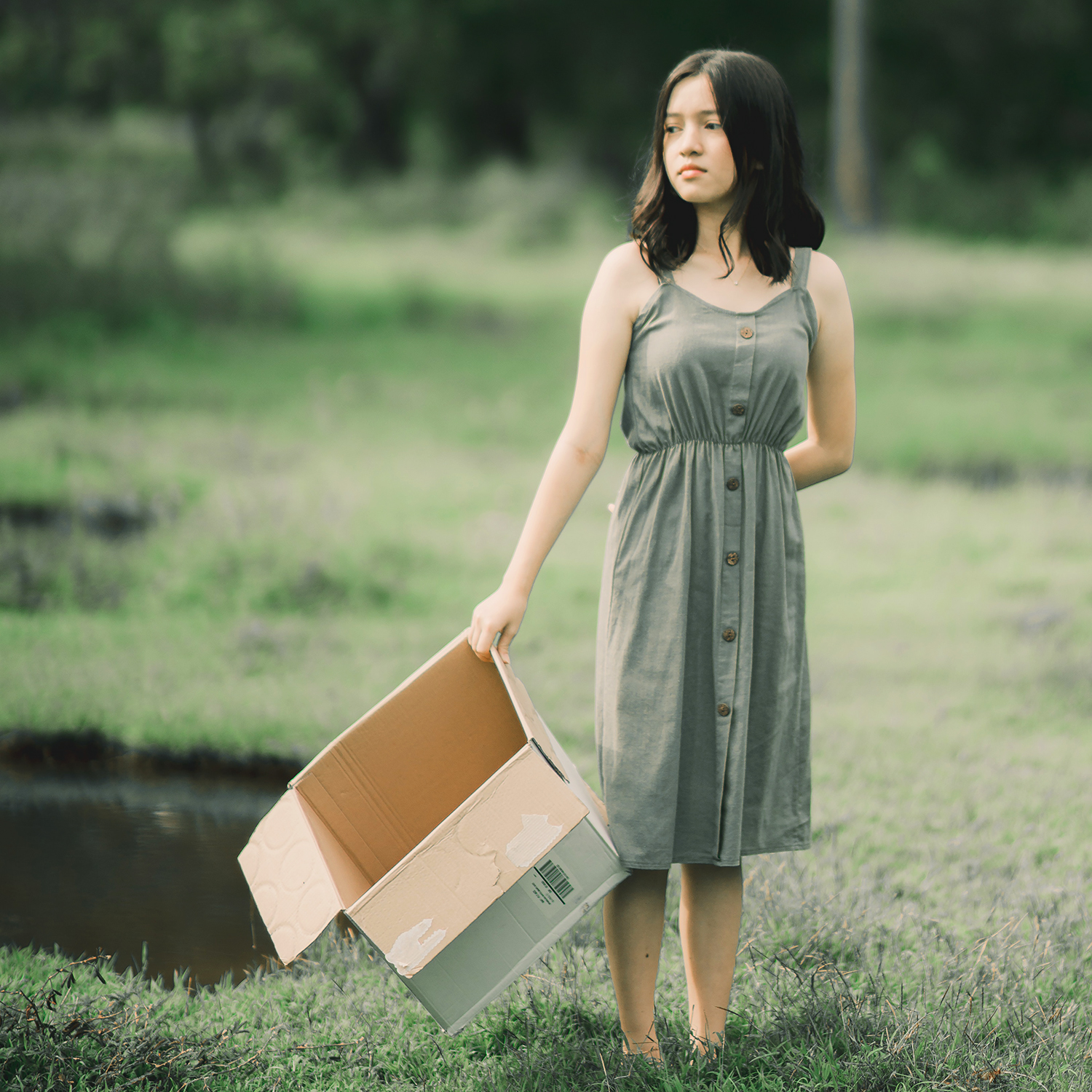 Woman with box in meadow by ryanniel masucol via pexels